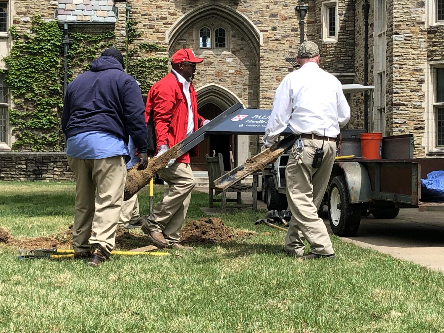 Physical Plant staff carry the Palmer Hall sign away while a small crowd observes in total silence.